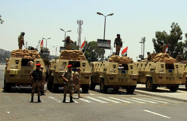 Egyptian Army armoured vehicles sit parked at a checkpoint in the district of Nasser City the morning after former Egyptian President Mohammed Morsi, the country