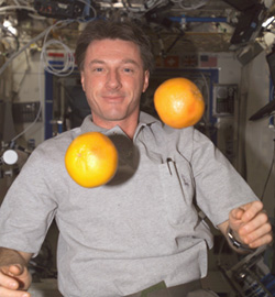 Astronaut C. Michael Foale on the ISS, with two grapefruits hovering in front of him.